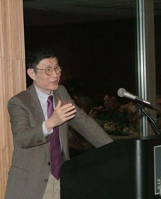 The late Professor Tung stands at a podium and speaks into a microphone.