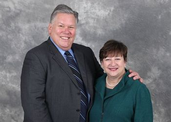 Jim and Sherry Bradow pose against a gray background
