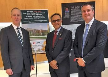 Dressed in dark gray suits, Lear executives and alumni Jason Cardew and Ray Scott pose for a photo with Sanjay Gupta, dean of the Eli Broad College of Business.
