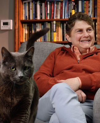 Sue Levy sits in a chair, with bookshelves in the background and her cat in the foreground