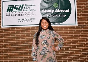 Selena Huapilla-Perez with the MSUFCU Study Abroad banner