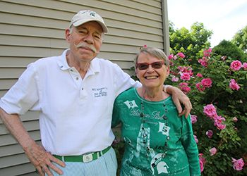 bill and sandy mason pose in front of their prized rosebushes